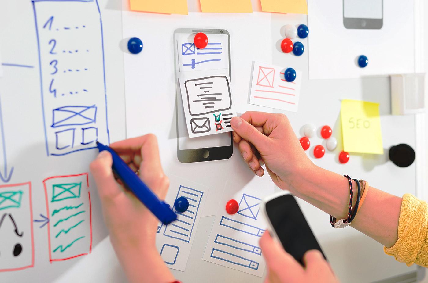 Foto van een whiteboard en drie handen die bezig zijn met het ontwerp van een app; een hand tekent een ontwerp met eenblauwe viltstift, een hand houdt een telefoon vast, en een hand houdt een papiertje met een getekend ontwerp tegen het whiteboard.
